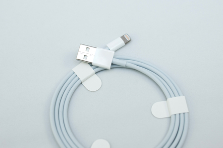 apple computers: PARIS, FRANCE - NOV 10, 2015:  Apple Computers  lighting cable on white with USB on the other side