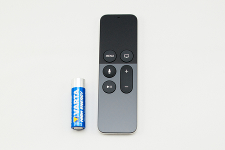 motion sensor: PARIS, FRANCE - NOV 10, 2015: New Apple TV media streaming  player microconsole by Apple Computers futuristic touch remote swipe-to-select with integrated Siri and motion sensor next to Varta High Energy battery to compare the size