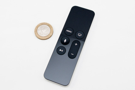 motion sensor: PARIS, FRANCE - NOV 10, 2015: New Apple TV media streaming  player microconsole by Apple Computers futuristic touch remote swipe-to-select with integrated Siri and motion sensor next to Two Pounds coin