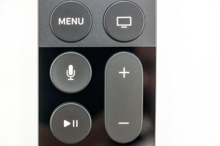 motion sensor: PARIS, FRANCE - NOV 10, 2015: Extreme colseup of the New Apple TV media streaming  player microconsole by Apple Computers futuristic touch remote swipe-to-select with integrated Siri and motion sensor - front view