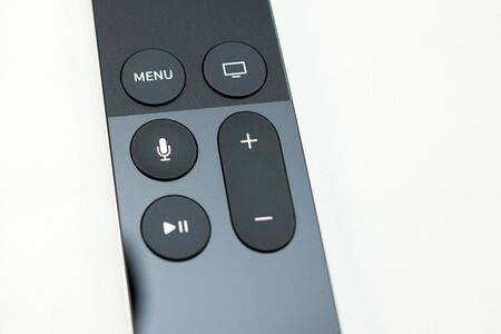 motion sensor: PARIS, FRANCE - NOV 10, 2015: Extreme colseup of the New Apple TV media streaming  player microconsole by Apple Computers futuristic touch remote swipe-to-select with integrated Siri and motion sensor - perspective view