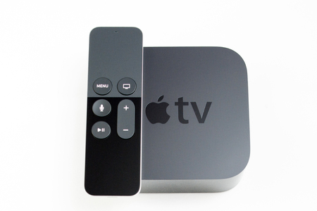 motion sensor: PARIS, FRANCE - NOV 10, 2015: New Apple TV media streaming  player microconsole by Apple Computers and the new touch remote swipe-to-select with integrated Siri and motion sensor leaning on the main box