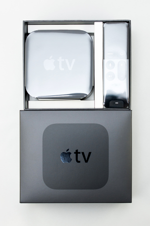 motion sensor: PARIS, FRANCE - NOV 10, 2015: New Apple TV media streaming  player microconsole by Apple Computers - unboxing process from above. It has new touch remote swipe-to-select with integrated Siri and motion sensor
