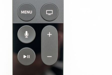 motion sensor: PARIS, FRANCE - NOV 10, 2015: Extreme colseup of the New Apple TV media streaming  player microconsole by Apple Computers futuristic touch remote swipe-to-select with integrated Siri and motion sensor, front view