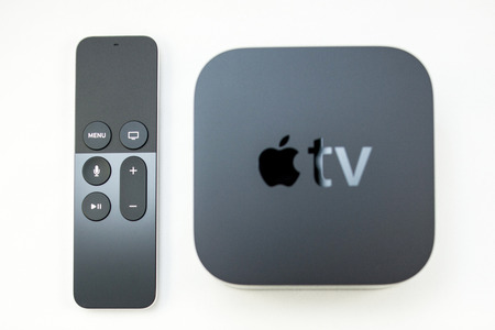 motion sensor: PARIS, FRANCE - NOV 10, 2015: New Apple TV media streaming  player microconsole by Apple Computers next to the new touch remote swipe-to-select with integrated Siri and motion sensor on white Editorial