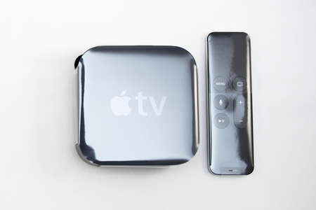 motion sensor: PARIS, FRANCE - NOV 10, 2015: New Apple TV media streaming  player microconsole by Apple Computers - unboxing from plastic film. It has new touch remote swipe-to-select with integrated Siri and motion sensor