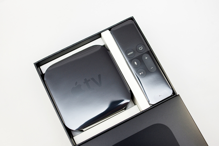 motion sensor: PARIS, FRANCE - NOV 10, 2015: New Apple TV media streaming  player microconsole by Apple Computers - unboxing from above. It has new touch remote swipe-to-select with integrated Siri and motion sensor Editorial