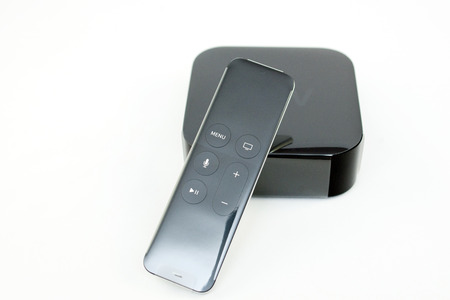 motion sensor: PARIS, FRANCE - NOV 10, 2015: New Apple TV media streaming  player microconsole by Apple Computers with the new touch remote swipe-to-select with integrated Siri and motion sensor covered in plastic film - unboxing process