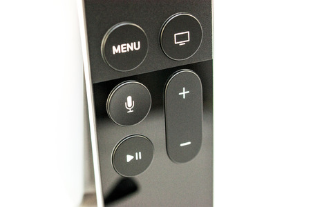 motion sensor: PARIS, FRANCE - NOV 10, 2015: Extreme colseup of the New Apple TV media streaming  player microconsole by Apple Computers futuristic touch remote swipe-to-select with integrated Siri and motion sensor - left lateral view