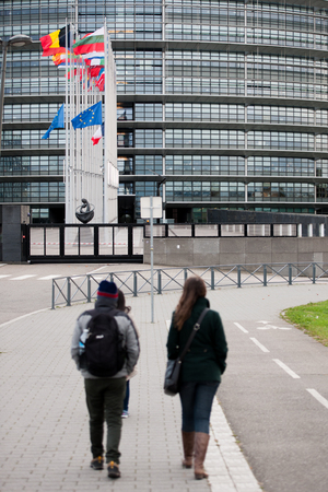 justice for all: STRASBOURG, FRANCE - 14 Nov 2015: Tourists admiring as European Union Flags and France flag flies at half-mast in front of the European Parliament building following an terrorist attack in Paris Editorial
