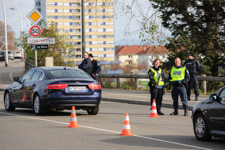 counter terrorism: STRASBOURG, FRANCE - NOV 14 2015: French Police with machine gun checking vehicles on the Bridge of Europe between Strasbourg and Kehl Germany, as a security measure in the wake of attacks in Paris Editorial