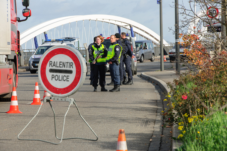 mobilization: STRASBOURG, FRANCE - NOV 14 2015: French Police checking vehicles on the Bridge of Europe between Strasbourg and Kehl Germany, as a security measure in the wake of attacks in Paris - slow down sign Editorial