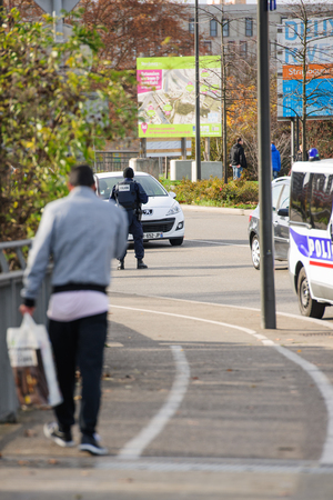 mobilization: STRASBOURG, FRANCE - NOV 14 2015: French Police checking vehicles on the Bridge of Europe between Strasbourg and Kehl Germany, as a security measure in the wake of attacks in Paris - man waling toward follice