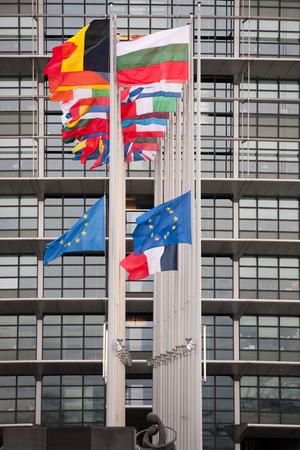 european parliament: STRASBOURG, FRANCE - 14 Nov 2015: European Union Flags and France flag flies at half-mast in front of the European Parliament building following an terrorist attack in Paris