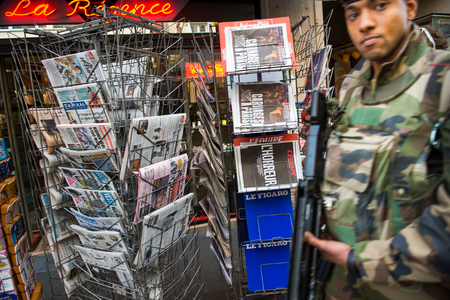 vigil: STRASBOURG, FRANCE - 14 NOV, 2015: French solider walking in front of the Press Kiosk with the front covers of International newspapers display headlining the terrorist attacks yesterday in Paris