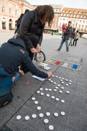 shootings: STRASBOURG, FRANCE - 14 NOV 2015: Light candles near General Kleber statue in tribute to the victims of the terrorist attacks in Paris - people writing PEACE word with candles Editorial