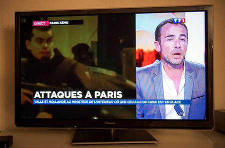 mobilization: PARIS, FRANCE - NOV 13, 2013: French Television reporting live as rescuers working on the schene of the attack. At least 40 people were killed across Paris, with explosions outside the national stadium where France was hosting German team Editorial