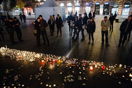 symbol victim: STRASBOURG, FRANCE - 14 NOV 2015: People looking at candles during a vigil in the center of Strasbourg for the victims of the November 13 attacks in Paris that killed at least 128 people Editorial