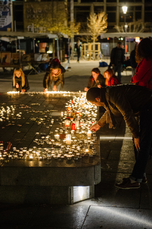 vigil: STRASBOURG, FRANCE - 14 NOV 2015: People attend a vigil and light multiple candles in the center of Strasbourg for the victims of the November 13 attacks in Paris that killed at least 128 people