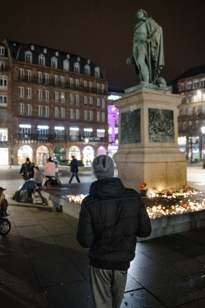 vigil: STRASBOURG, FRANCE - 14 NOV 2015: Man with headphones attend a vigil and light candles in the center of Strasbourg for the victims of the November 13 attacks in Paris that killed at least 128 people