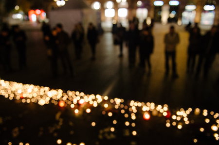 symbol victim: Defocused view of people attend a vigil and light candles in the center of Strasbourg for the victims of the November 13 attacks in Paris that killed at least 128 people Editorial