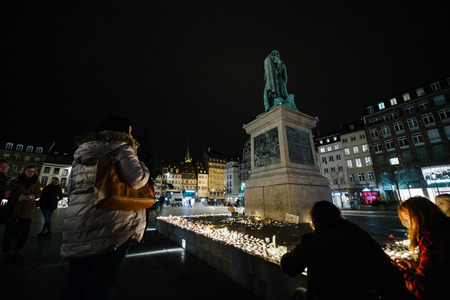 vigil: STRASBOURG, FRANCE - 14 NOV 2015: People attend a vigil and light candles in the center of Strasbourg under Gerneral Kleber statue for the victims of the November 13 attacks in Paris that killed at least 128 people Editorial