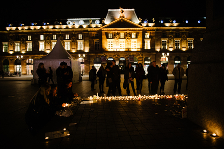 law breaking: STRASBOURG, FRANCE - 14 NOV 2015: People attend a vigil and light candles in the center of Strasbourg for the victims of the November 13 attacks in Paris that killed at least 128 people