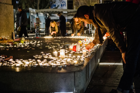 vigil: STRASBOURG, FRANCE - 14 NOV 2015: People attend a vigil and light candles in the center of Strasbourg for the victims of the November 13 attacks in Paris that killed at least 128 people