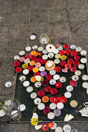 mobilization: STRASBOURG, FRANCE - NOV 16, 2015: Messages, candles in shape of heart and flowers are left around General Kleber statue in memorial for the victims of the Paris Attacks.