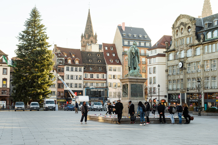 mobilization: STRASBOURG, FRANCE - NOV 16, 2015: People looking at messages, candles and flowers are left around General Kleber statue in memorial for the victims of the Paris Attacks.