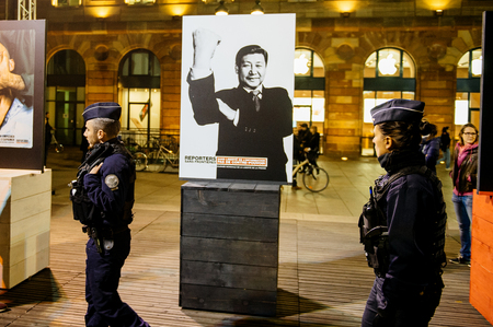 equivalent: STRASBOURG, FRANCE - NOV 18, 2015: Reporters Without Borders exposing the campaign depicting world-famous dictators giving everyone the finger, or the international equivalent thereof in the cneter of Strasbourg