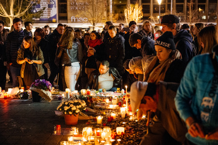 vigil: STRASBOURG, FRANCE - NOV 18, 2015: People gathering, placing flowers, messages and candles in center of Strasbourg, in solidarity for victims and families of the assault in Paris