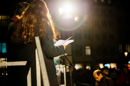 vigil: STRASBOURG, FRANCE - NOV 18, 2015: People reading from the stage the names of the victims of the assault in Paris Editorial