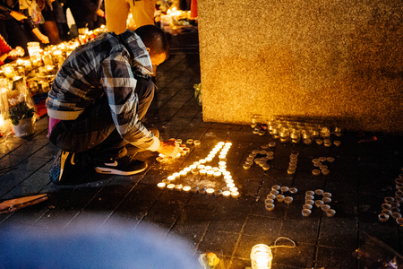 vigil: STRASBOURG, FRANCE - NOV 18, 2015: Man making Eiffel Tower from candles in center of Strasbourg, in solidarity for victims and families of the assault in Paris