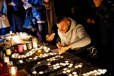 vigil: STRASBOURG, FRANCE - NOV 18, 2015: Man writing Parisr from candles in center of Strasbourg, in solidarity for victims and families of the assault in Paris