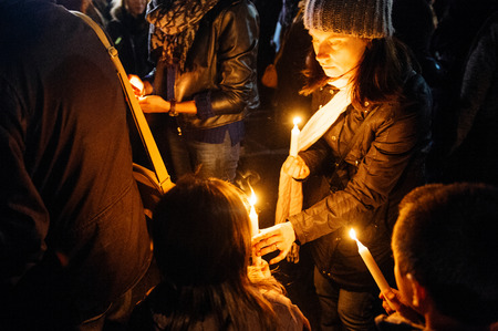 vigil: STRASBOURG, FRANCE - NOV 18, 2015: Mother with childs lights candles in center of Strasbourg, in solidarity for victims and families of the assault in Paris Editorial