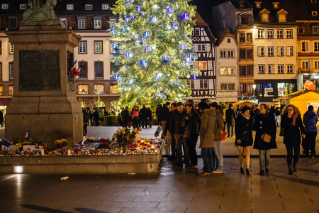 christkindlmarkt: STRASBOURG, FRANCE - NOV 28, 2015: Busy Christmas Market Christkindlmarkt in the city of Strasbourg, Alsace region,  France with people looking at candles after Attacks in Paris with Christms tree behind