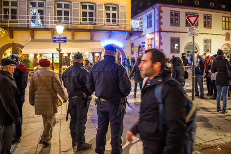 christkindlmarkt: STRASBOURG, FRANCE - NOV 28, 2015: Busy Christmas Market Christkindlmarkt in the city of Strasbourg, Alsace region,  France with Police patrol the streets following the terrorist attacks on November 13 in Paris Editorial