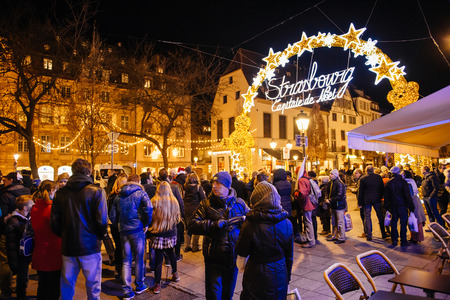 christkindlmarkt: STRASBOURG, FRANCE - NOV 28, 2015: Busy Christmas Market Christkindlmarkt in the city of Strasbourg, Alsace region,  France with people admiring Capitale de Noel sign Editorial