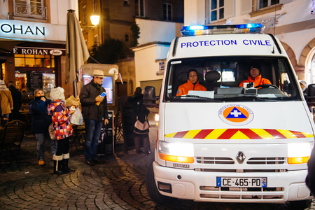 christkindlmarkt: STRASBOURG, FRANCE - NOV 28, 2015: Busy Christmas Market Christkindlmarkt in the city of Strasbourg, Alsace region,  France with Civil Protection truck surveilling city streets