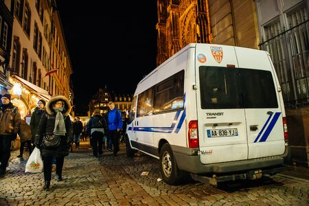 christkindlmarkt: STRASBOURG, FRANCE - NOV 28, 2015: Busy Christmas Market Christkindlmarkt in the city of Strasbourg, Alsace region,  France with Police car patrol the streets following the terrorist attacks on November 13 in Paris