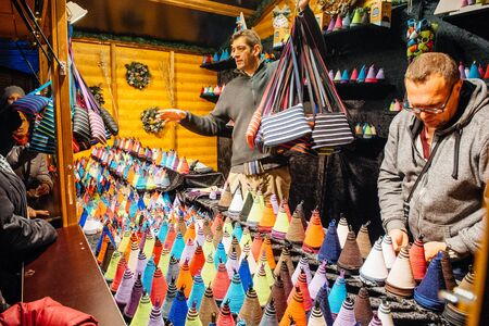 christkindlmarkt: STRASBOURG, FRANCE - NOV 28, 2015: Busy Christmas Market Christkindlmarkt in the city of Strasbourg, Alsace region,  France with man selling souvenirs Editorial