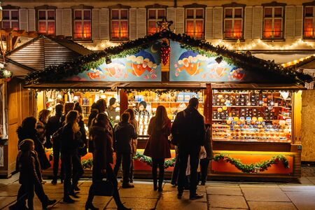 strasbourg: Busy Christmas Market Christkindlmarkt in the city of Strasbourg, Alsace region,  France with people admiring gifts at kiosk