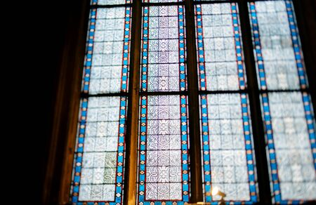 obtain: PARIS, FRANCE - JANUARY 23, 2013: Stained glass with beautiful floral ornament seen with a tilt-shift lens to obtain the defocused effect