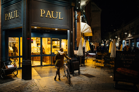 patisserie: STRASBOURG, FRANCE - NOV 18, 2015: Paul Boulangerie Et Patisserie cafe with open doors and women on bike waiting for her friend. Paul is a French chain of bakerycafe restaurants established in 1889 in the city of Croix, in Northern France Editorial