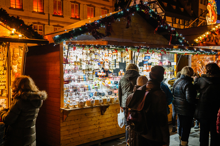 christkindlmarkt: STRASBOURG, FRANCe - NOV 28, 2015: Tourists walking between chalets during Strasbourg Christmas Market Christkindlmarkt, buying souvenirs, admiring toys and drinkging mulled wine. Strasbourg Christmas Market is considered one of the most beautiful in the  Editorial