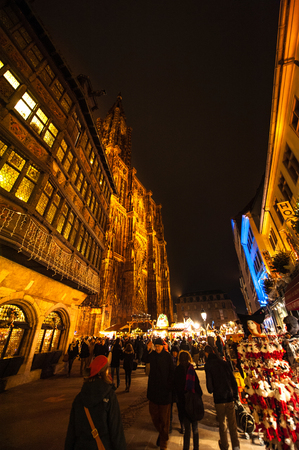 full lenght: STRASBOURG, FRANCE - NOVEMBER 29, 2014: Full lenght Strasbourg Cathedral with People walking among Christmas stands during the winter Christmas Market on November 29, 2012 in Strasbourg. Strasbourg Christmas Market is considered to be the oldest and the m