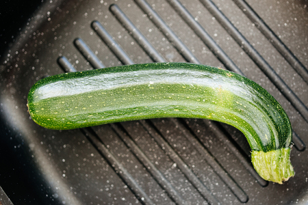 dripping pan: Organic zucchini in grill pan seen from above