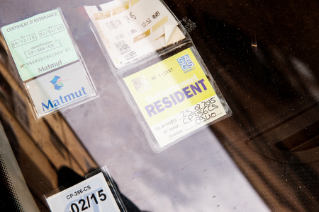 parking violation: MARSEILLE, FRANCE - JULY 19, 2014: Close-up of diverse parking tickets on cars windshield with special permit to park the car as a resident