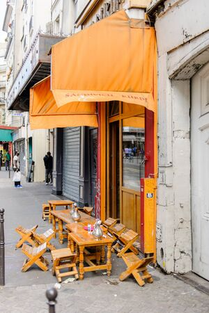french ethnicity: PARIS, FRANCE - 18 AUG 2014: Street cafe with chairs on the streets of Paris, France with people talking at the mobile phone in the background